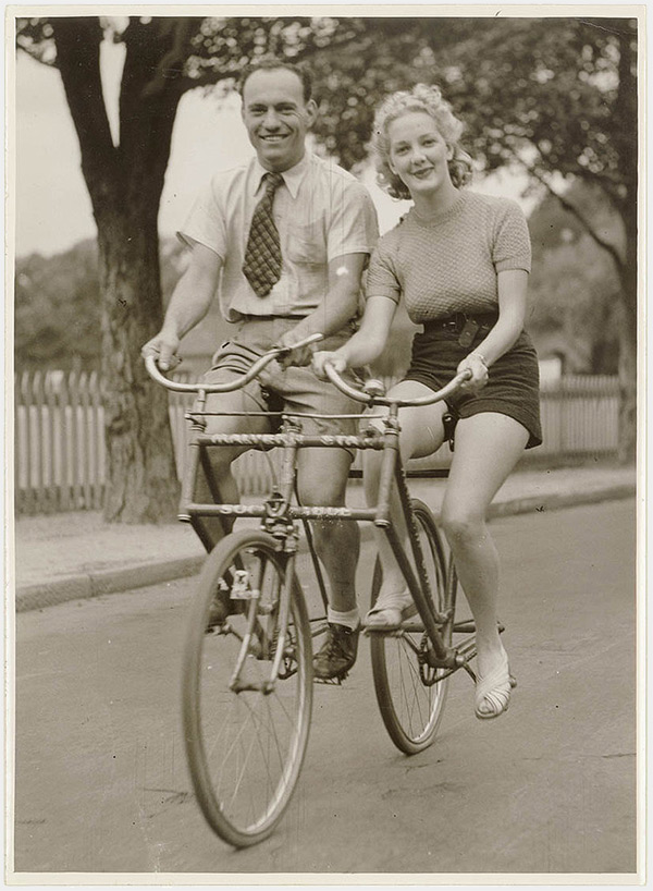 Man and woman on a MalvernStar abreast tandem bicycle