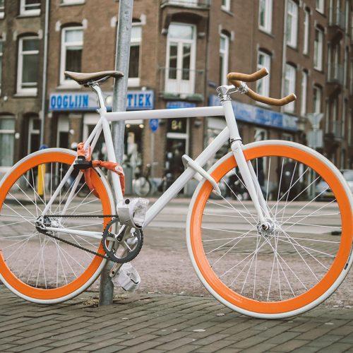 White fixie bike with orange rims