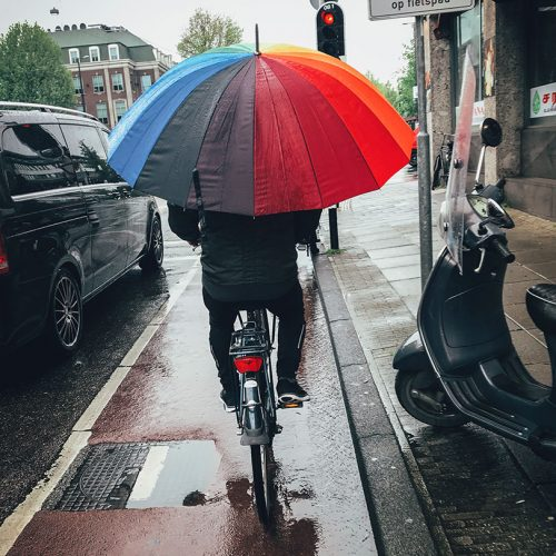 Riding a bike with a multi-colored umbrella