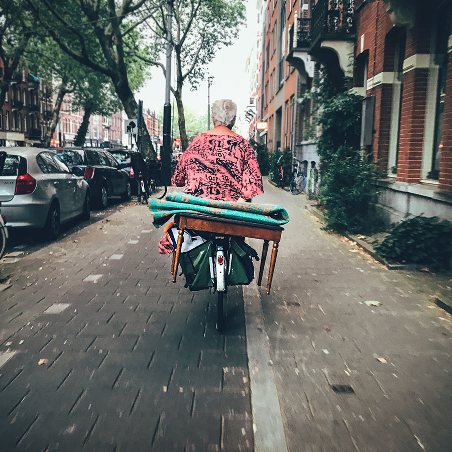Elderly lady carrying table on a bicycle