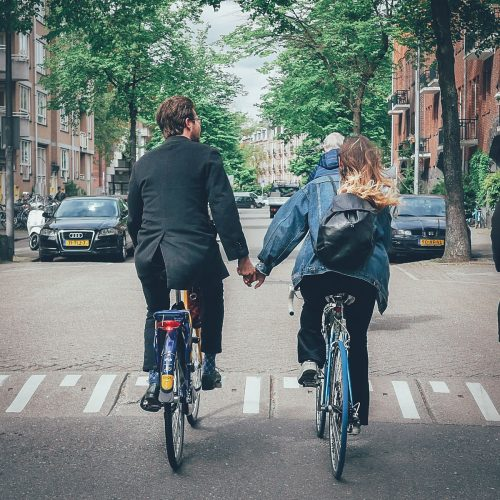 Couple holding hands while cycling