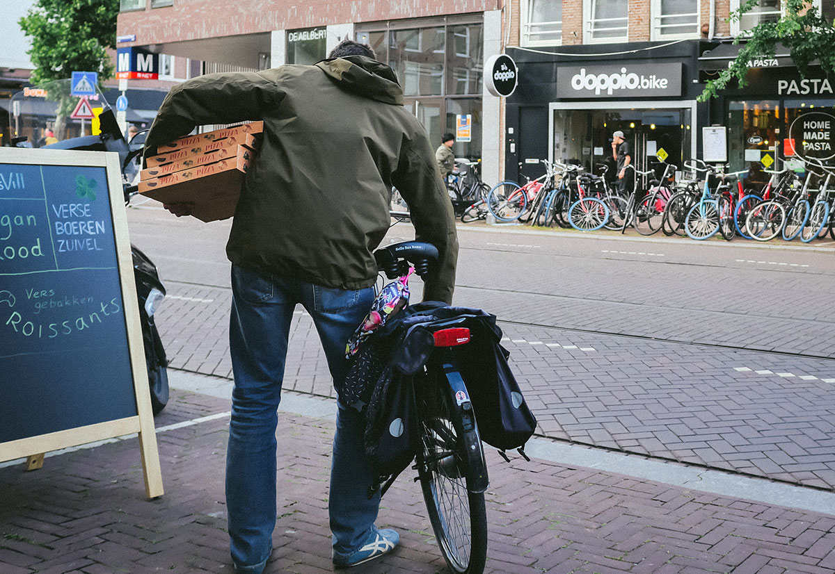 Man picking up his pizza order on bike during COVID-19