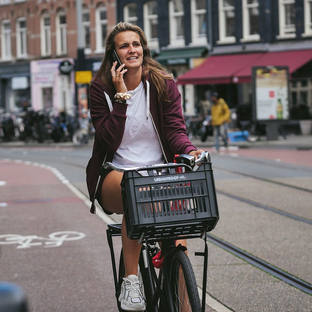 Girl riding a bicycle with a milk crate and talking on the phone