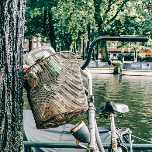 Wire mesh bicycle basket turns into garbage bin.
