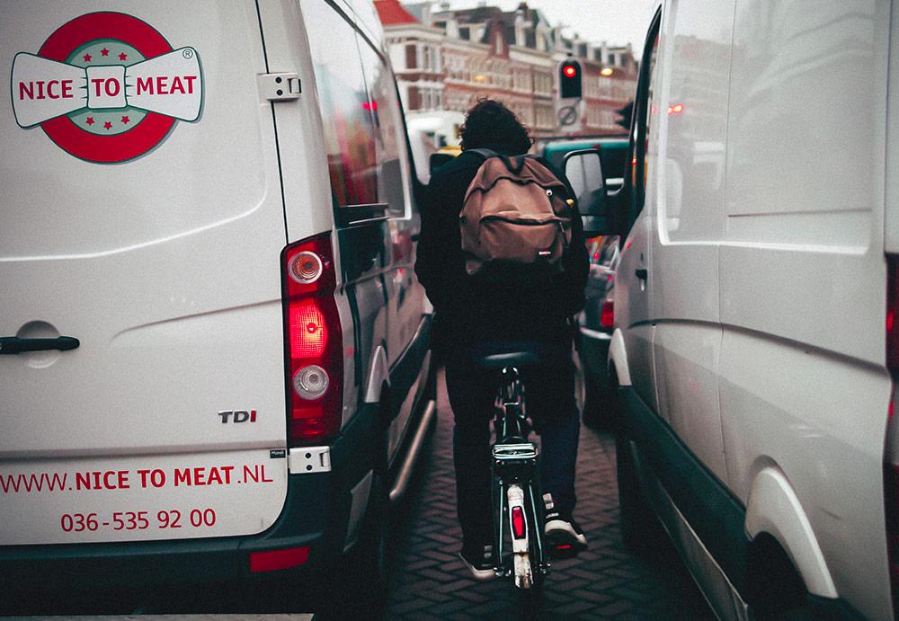 Man squeezing through traffic on a bike