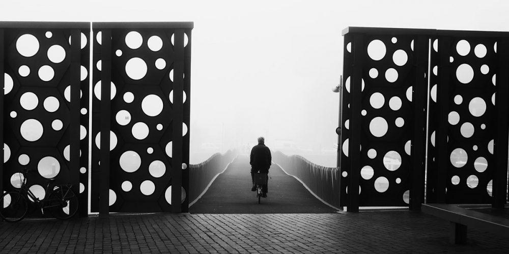 Riding a bike across the bridge with fog