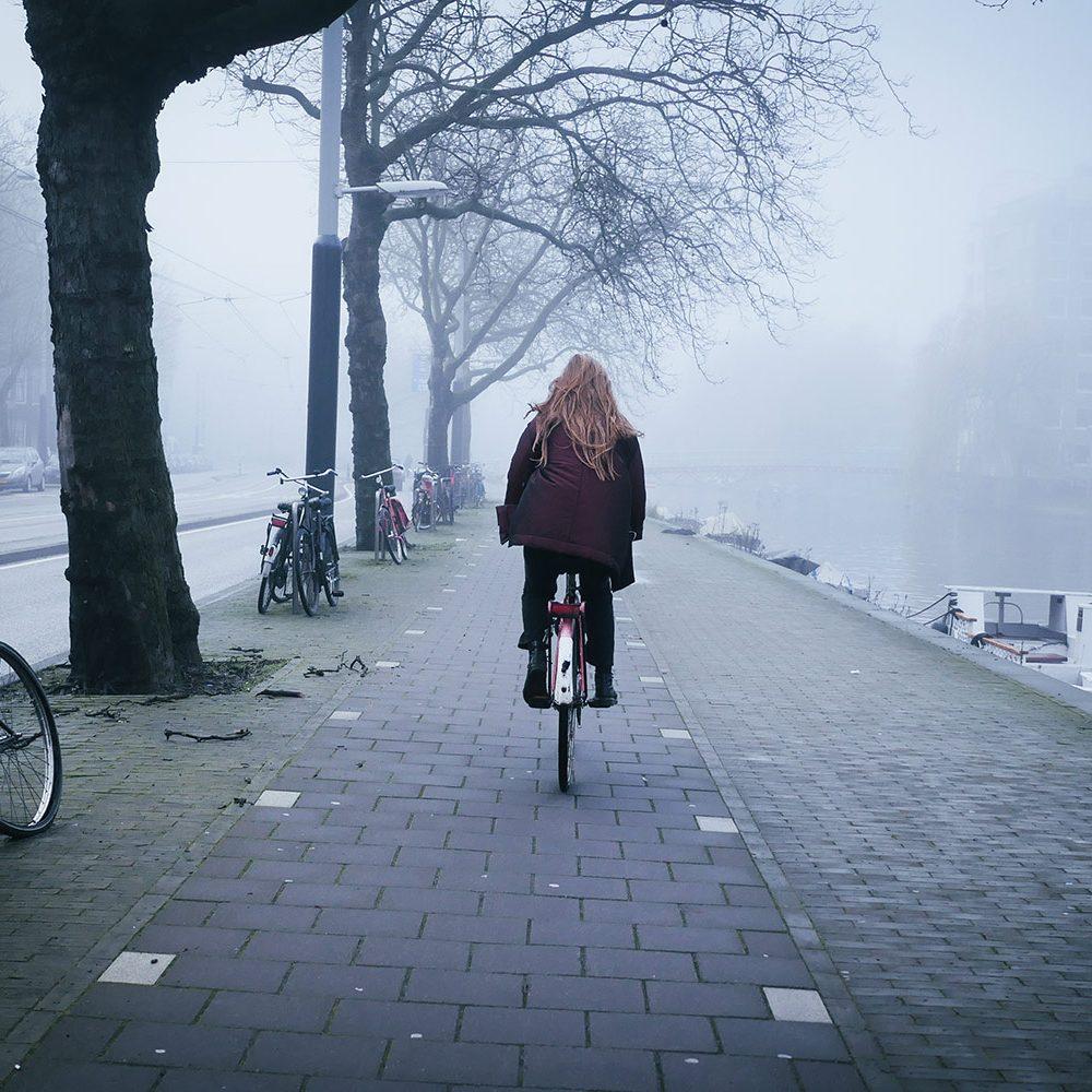 Girl riding bike in the fog