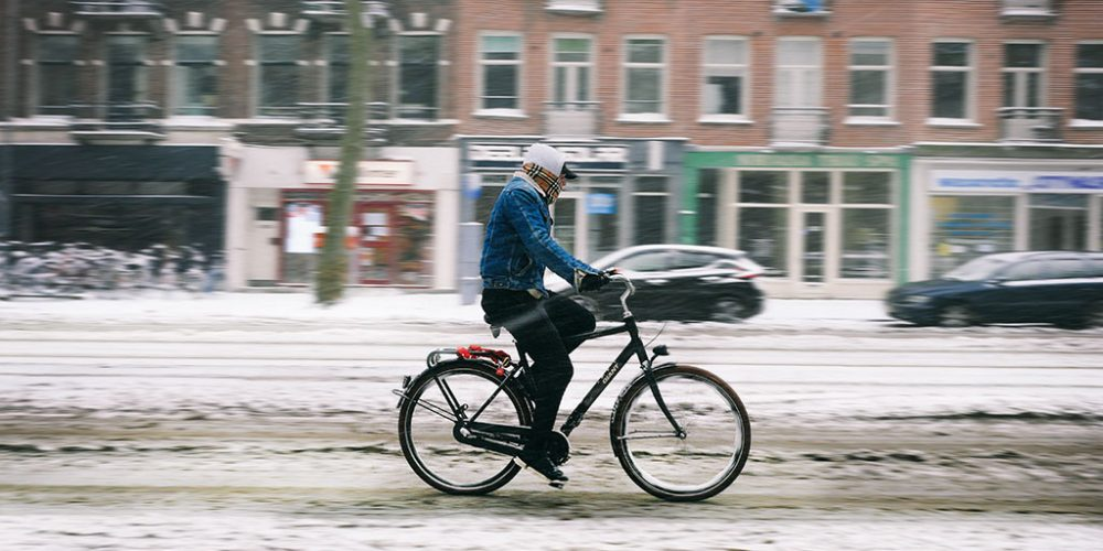 Riding a bicycle in snow in Amsterdam