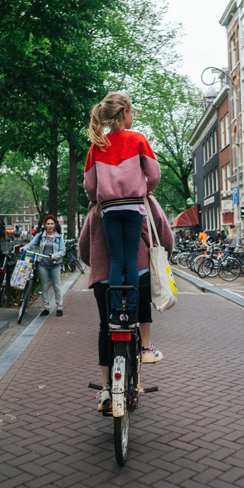 Young girl standing on bicycle back rack
