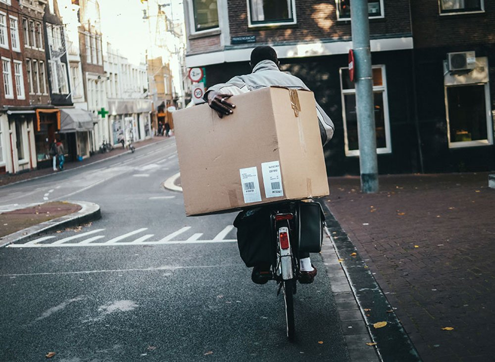 Man carrying a large box on back rack in Amsterdam